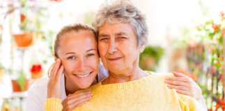 female caregiver and senior woman are smiling