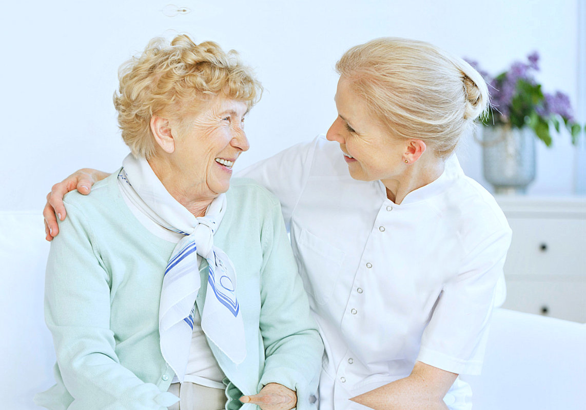 senior woman and caregiver looking at each other while smiling