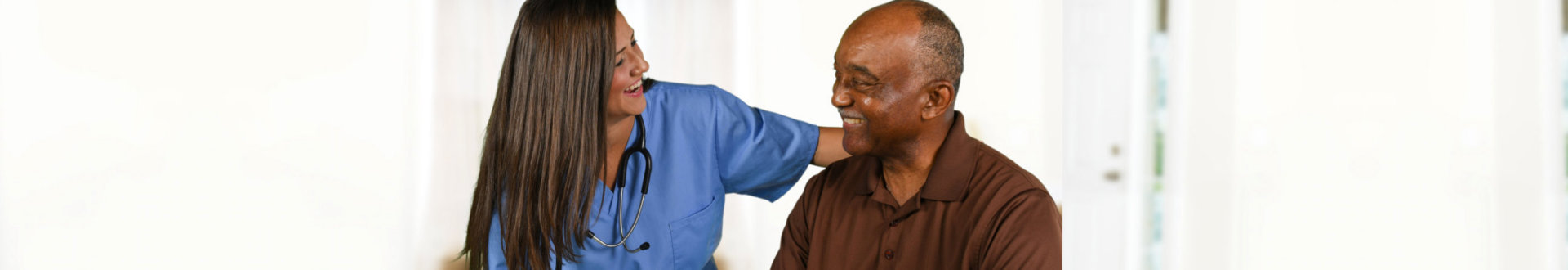 senior man and female caregiver are looking at each other while smiling