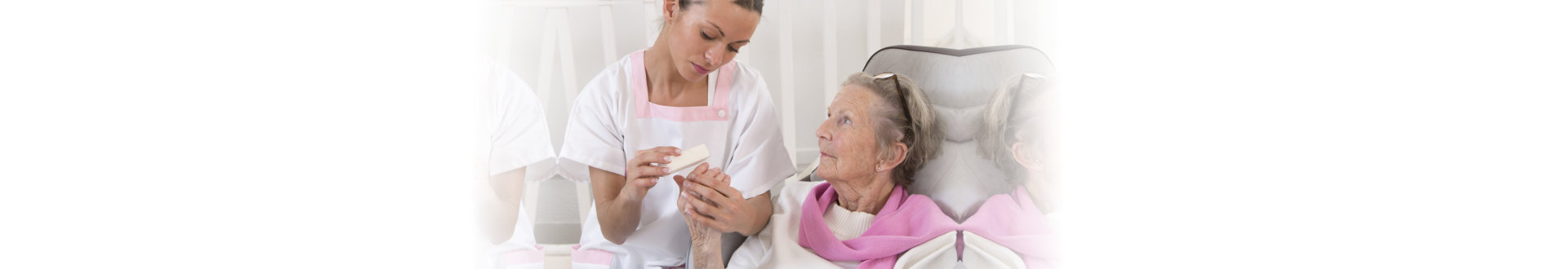 senior women receiving home beauty treatment hand care
